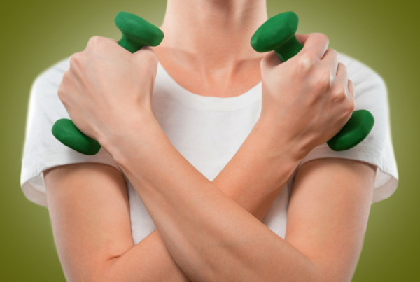 Woman holds dumbbells, arms crossed, face is not visible